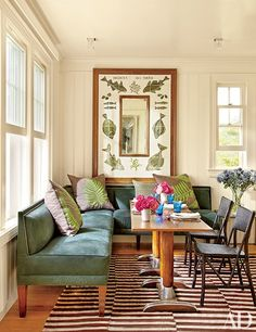 A breakfast room with a custom banquette clad in green suede and vintage bistro tables | archdigest.com