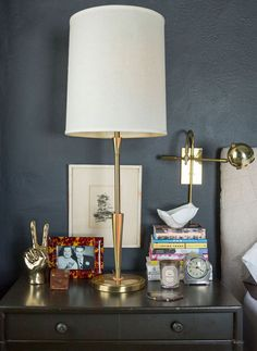 The cloudy effect of Matt Carollo's bedroom walls was produced with Benjamin Moore Chalkboard paint. Brass decor pops against the moody hue.   Lonny