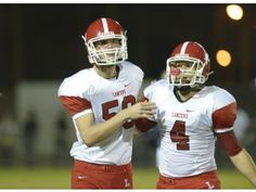 Article Tab: Jake Olson, the long snapper for Orange Lutheran High, left, is guided off the field by teammate Adam Connette after a play against St. John Bosco in Bellflower. Olson is blind, yet he plays football, golf and is a motivational speaker.