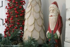 Burlap and glitter tree, red berry tree and hand-carved Santa. Traditional red and green Christmas decor.