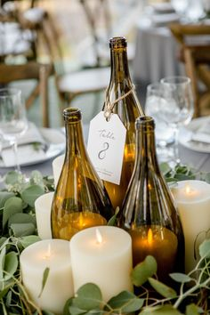 Wine bottle candle lanterns, candles and greenery make for a simple and beautiful centerpiece.