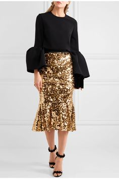 DOLCE & GABBANA Ruffled sequined tulle skirt $1,575 Dolce & Gabbana's skirt has been crafted in Italy from mid-weight gold tulle, enriched with scores of glistening sequins - a brand signature. Detailed with a black elasticated band to create definition at the waist, it's finished with a gently fluted hem that captures the collection's joyful spirit. Team yours with minimalist pumps or sandals.  Shown here with: Roksanda Top, Aerin Beauty Clutch, Alaïa Sandals, Marni Ring, Etro Earrings.