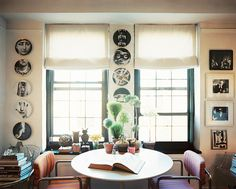 Dining Room Photo - A round table and a pair of chairs below a collection of Fornasetti plates