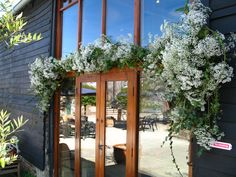 Upwaltham Barn, entrance to the East Barn decorated with clouds of white gypsophilia. Flowers by Spriggs Florist, www.spriggs-florist.co.uk