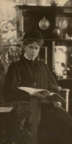 """Grã-duquesa Elizabeth Feodorovna em 1906. Ela está sentada em uma cadeira padronizada com um livro aberto. Ela está vestindo roupas de luto escuros e uma cruz em uma fita em volta do pescoço. Há um aparador atrás dela. A fotografia é assinada e datada """"Ella 1906 'em lápis."""