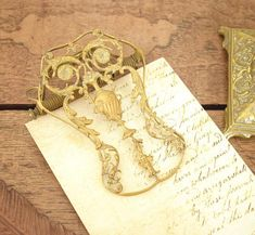Vintage metal paper or letter clip, ornate and decorative Rococo style