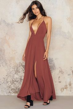 This dress will blow your mind away! The Cross Strap Slit Dress by NA-KD Party comes in dusty red and features a cross strap dress with slit, maxi length and open back. Style with heels and a small clutch!