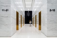 Gold mirrored lift reveals by Fogarty Finger » 437 Madison Avenue: