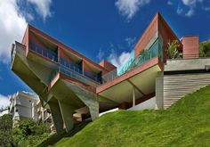 Brazilian firm Anastasia Architects designed this slope house plan on a 30-degree incline with dramatic cantilever overhangs that add a sculptural element while highlighting the home's precarious position. Due to the steep angle of the land, the main floor is buried 7 meters below-grade at street side, providing privacy for the residents, while at the opposite side of the house the valley and forest views are wide open behind floor-to-ceiling glass walls.