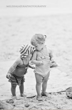Little sister giving big sis a little kissy at the beach.  Sweet!