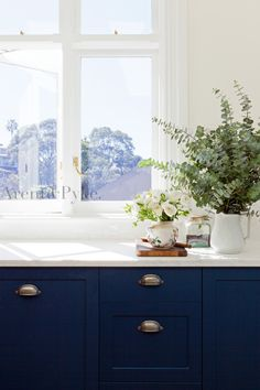 Navy lower cabinets. Neutral walls. Bronzed hardware.