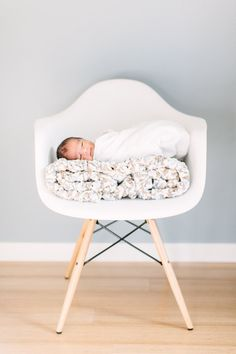 Cute idea for the modern new mom - Modern newborn photos with Eames Chair.