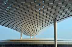 The amorphous structural roof is supported infrequently by relatively slender columns