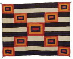 NAVAJO TRANSITIONAL BLANKET    softly woven, in natural ivory and dark brown, and aniline blue, red and orange, with a stylized Chief's Third Phase design, composed of nine concentric squares overlaying a banded and striped ground.  69 in. by 56 in.
