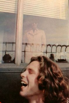 ...2 unusual things...Jim Morrison laughing out loud & Ray Manzarek reflected in the window. Great photo!