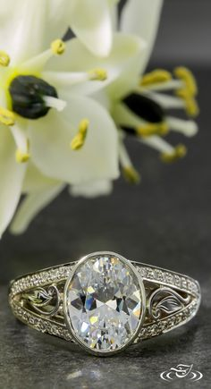 An oval and antique leaf engraved engagement ring. Green Lake Jewelry