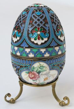 Russian silver enameled egg box having floral design miniatures. Gold wash interior. Includes Russian silver stand. Piece holds Cyrillic Pavel Akimov Ovchinnikov workmaster marks.