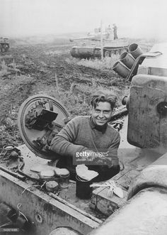 The radio/machine gun operator of a Tiger I rests with other Tiger crews during a lull in combat