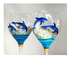 Designed and hand painted glassware featuring two blue dolphins on each wine glass goblet jumping above breaking waves scrolled in frosted shimmering silver and gold above layered glossy ocean turquoi