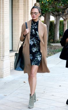 Chrissy Teigen wears floral mini dress, camel coat, green ankle boots with aviators and a top knot.