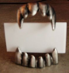 Food marker cards...get cheap plastic fangs and spray paint them silver