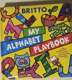 """Beautiful, Bold, Vibrant Board Book, """"My Alphabet Playbook"""" by Romero BrittoA unique piece by world famous pop artist Romero Britto brings the alphabet to life in this never-before-used bold and beautiful puzzle board book!  As children read the book they can guess which object is hiding under each press-out letter, and with the help of enclosed stands, they can stack the letters to make their own vibrant sculptures! A modern-day pop-culture icon, Romero Britto is one of the premier pop…"""
