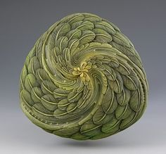 Wood Carvings. sculpture by jacques vesery carving of feathers swirling around a central point.