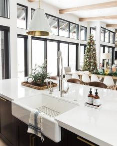 Instagram photo by @studiomcgee • 818 likes - amazing white kitchen island overlooking a sun lit family room with a wall of black framed windows and a christmas tree.