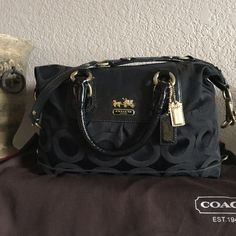 "authentic coach • madison sabrina satchel Coach Madison Op Art Sabrina Satin Satchel. Black with gold hardware. Zip top closure. Bottom has four feet for protection (normal wear on these, see photos). Inside is solid purple with one zip pocket, one slip pocket and ""D"" ring. There are a couple very small spots on the inside (see photos). Measures approx. 12"" wide, 6"" high, 5.5"" deep. Double rolled leather handles have a 5"" drop. Comes with shoulder strap and dust bag. Purchased on another…"