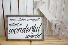 and I think to myself what a wonderful world. custom, smaller size, 16.5 x 10.5 wood sign. white with black writing.   distressed Wood sign with stained frame.  Each sign is hand painted, then lightly distressed to give it a beautiful worn look. Since no two pieces of wood are alike and distressing technique varies, no two signs will be exactly alike. I do not attempt to conceal the woods raw beauty, which includes, nicks, knots, & other natural imperfections.   Each sign comes with hangi...
