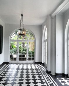 Stunning black and white checkerboard floors and floor to ceiling arched windows.