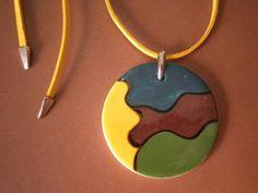 Mandala de cerâmica pintada à mão, esmaltada e queimada.  Colar com aprox. 48 cm de comprimento.  Mandala: 5 x 5 cm de diâmetro  O fio é de couro ecológico (camurça) na cor amarela, com finalizadores prata.  A peça é fixada com jacaré prata.  O tamanho pode ser ajustado.    Faça já sua encomenda !!