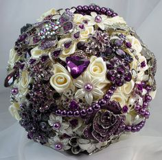 """www.etsy.com/...    This gorgeous bouquet has Aristocratic purple, plum and eggplant highlights and is adorned with ivory silk roses. Accented with silver and pearlized flair. It has a fashionable working frame that says Love Never Ends which can be used as is or will hold your most cherished photo. The handle is lovingly wrapped with """"French twist"""" style silky ivory ribbon which fits you..."""