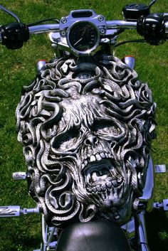 Snakes and screaming skull molded on bike tank. In gun metal gray.