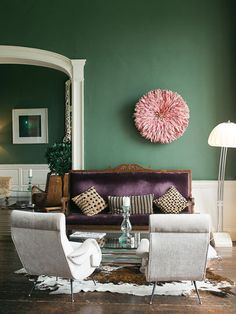 Not usually a green person, but I am a PURPLE person. Purple couch? Wow. The green really sets off the purple and pink accents, and I love the cowhide rug as an anchor (and as something a little more masculine to balance our the feminine stuf). via aparment therapy