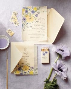 Lavender and yellow wedding invitation suite featuring watercolor violet anemones, golden ranunculus and garden roses by illustrator Sarah McCay.