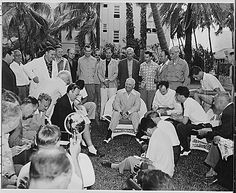 "Photograph of President Harry Truman holding a press conference on the lawn of the ""Little White House,"" his vacation residence at Key West, Florida, surrounded by reporters, photographers, and staff members., 03/30/1950"