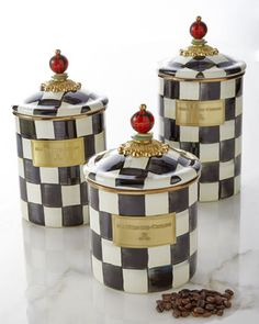 Canisters by MacKenzie-Childs® sport signature Courtly Check® pattern with a golden luster and red ball finials.