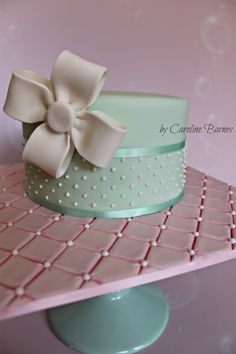 Polka dot cake with fondant bow and quilted cake board.