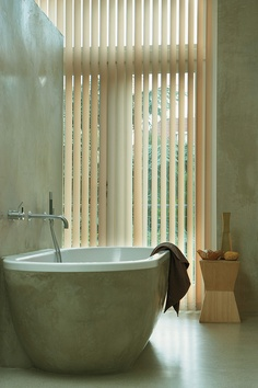 A serene bathroom with Vertical Solutions® Select Vertical Blinds ♦ Hunter Douglas Window Treatments