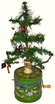 """C-1920 German Feather Tree on tin litho musical base. This beautiful Christmas feather Tree is fresh from 40 year collection that has been untouched for over 10 years Base is Near Mint condition with a plink-plink mechanism that also spins the tree around. Tree may have and older repair at bottom as there is some tape there? Ormaments were on it when I got it which is how it was displayed for many years. Tree is 10"""" tall Overall 14"""" tall"""