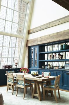 What a lovely ass dining room! Those windows are amazing! And all of the colors work together so well. Blue, light brown wood and white.