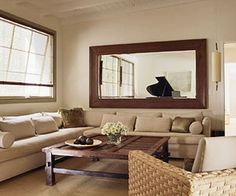 Horizontal mirror over couch echoes and reflects light from the window on the adjacent wall