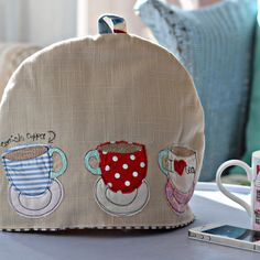 teacups - tea cosy - Size Approx in cm: 25 (h) x 30(d) (fits a standard family teapot)Material outer made from brushed cotton. Lining made from baby cord or cotton ticking. Padded with polyester wadding.Design detail Applique and freehand machine embroidery on front and back