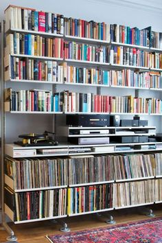 A faithful shelving system bearing its load of books, vinyl and audio equipment. Notice the semi-wall mounted structure with stabilizing feet for the heavy load