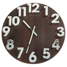 Casual yet eye-catching, this beautiful wall clock showcases a mid-century modern era motif with an espresso-tone wood grain dial sporting large 3D silvertone Arabic numerals. Powered by quartz movement, this clock requires one AA battery.