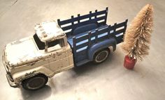 Fun old truck with bottle brush tree.