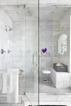 Beautiful clean white marble in this multihead shower is accented nicely with bright white linens, black and white flooring and rug with a violent pop of purple from the flowers in the vase. Beautiful!