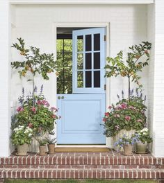 Front Porch Planter Ideas Blue front door, white brick house, with red brick porch steps. Wicker and Terra Cotta Planters with Citrus Trees and Flowers via Southern Living - Door Front Porch Planters, House With Porch, House Exterior, Front Door, Porch Planters, Front Porch Plants, Brick Porch, Doors, Door Color