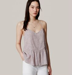 Dot-sprinkled, we're into the femme peplum and clean lines of this strappy essential. V-neck. Spaghetti straps. Slight racerback. Peplum hem.